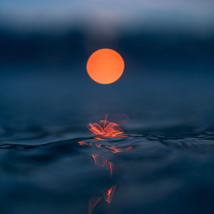 orange sun emerging over a water surface