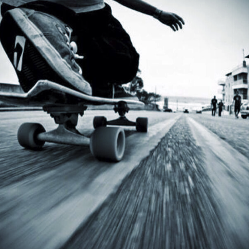 ground level angle of a skateboarder on a skateboard on a road riding towards a beach