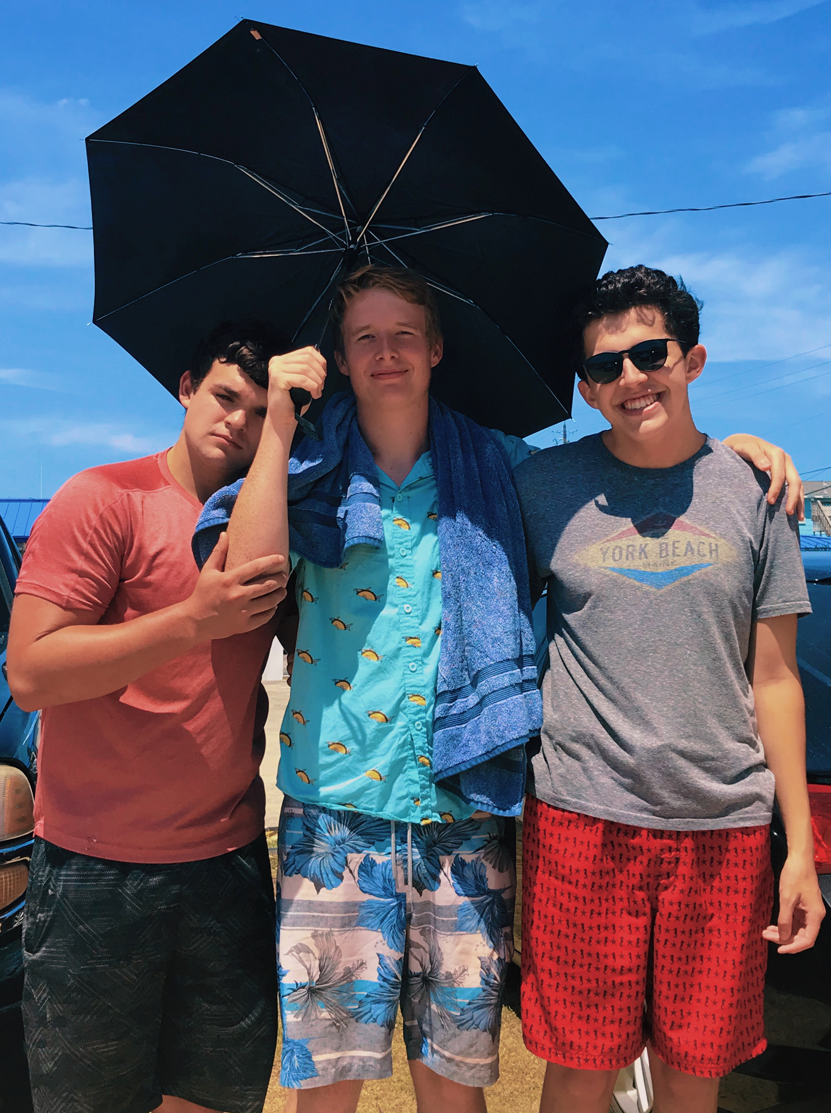 Calvin standing with two friends underneath umbrella smiling