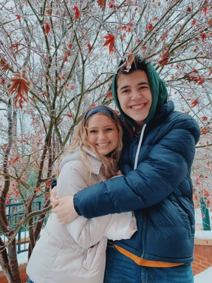 Two students hugging and smiling outside