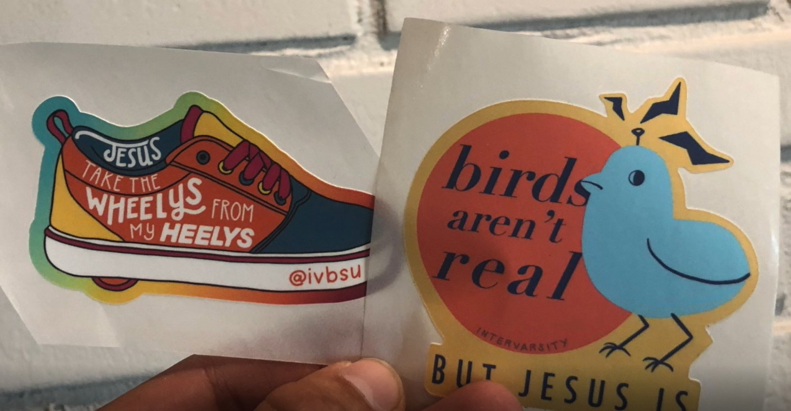 """Screenshot of stickers Matt's chapter sent to incoming freshmen. One is a shoe with"""" Jesus, take the wheelys from my heelys."""" And another is a bird with: """"Birds aren't real, but Jesus is."""""""