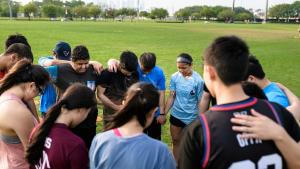 Group of Asian American students holding hands praying