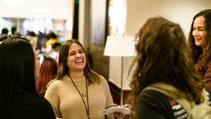 Group of four women talking and laughing in hotel hallway outside of conference session