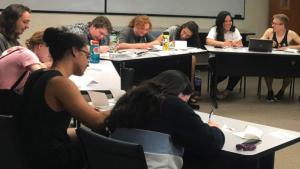 Group of students seated at tables writing letters to incoming freshmen