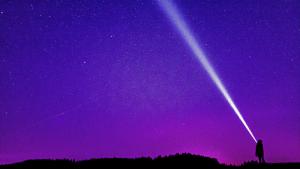 Person outside at night shining flashlight into purple sky