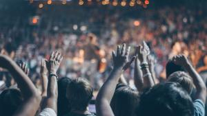 Group of people in auditorium with hands raised worshiping